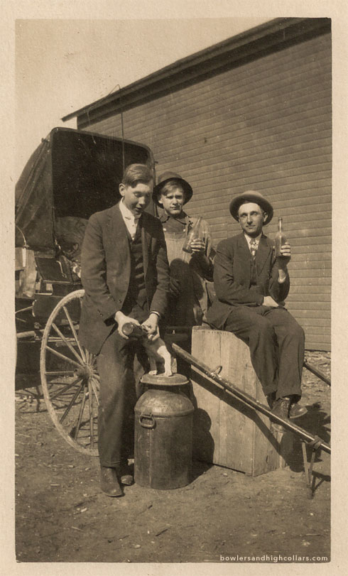 Giving the pup a drink by the wagon. RPPC. Private Collection.